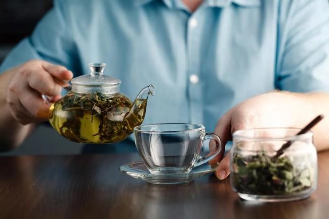 мужчина держит чайник с чаем