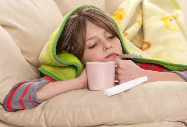 ребенок с градусником пьет чай