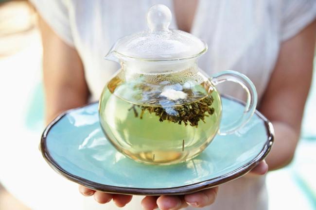 женщина держит заварник с зеленым чаем
